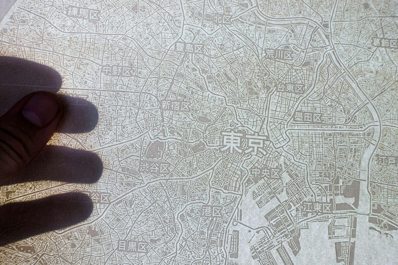 Light shines through the laser engraved paper map of Tokyo, Japan